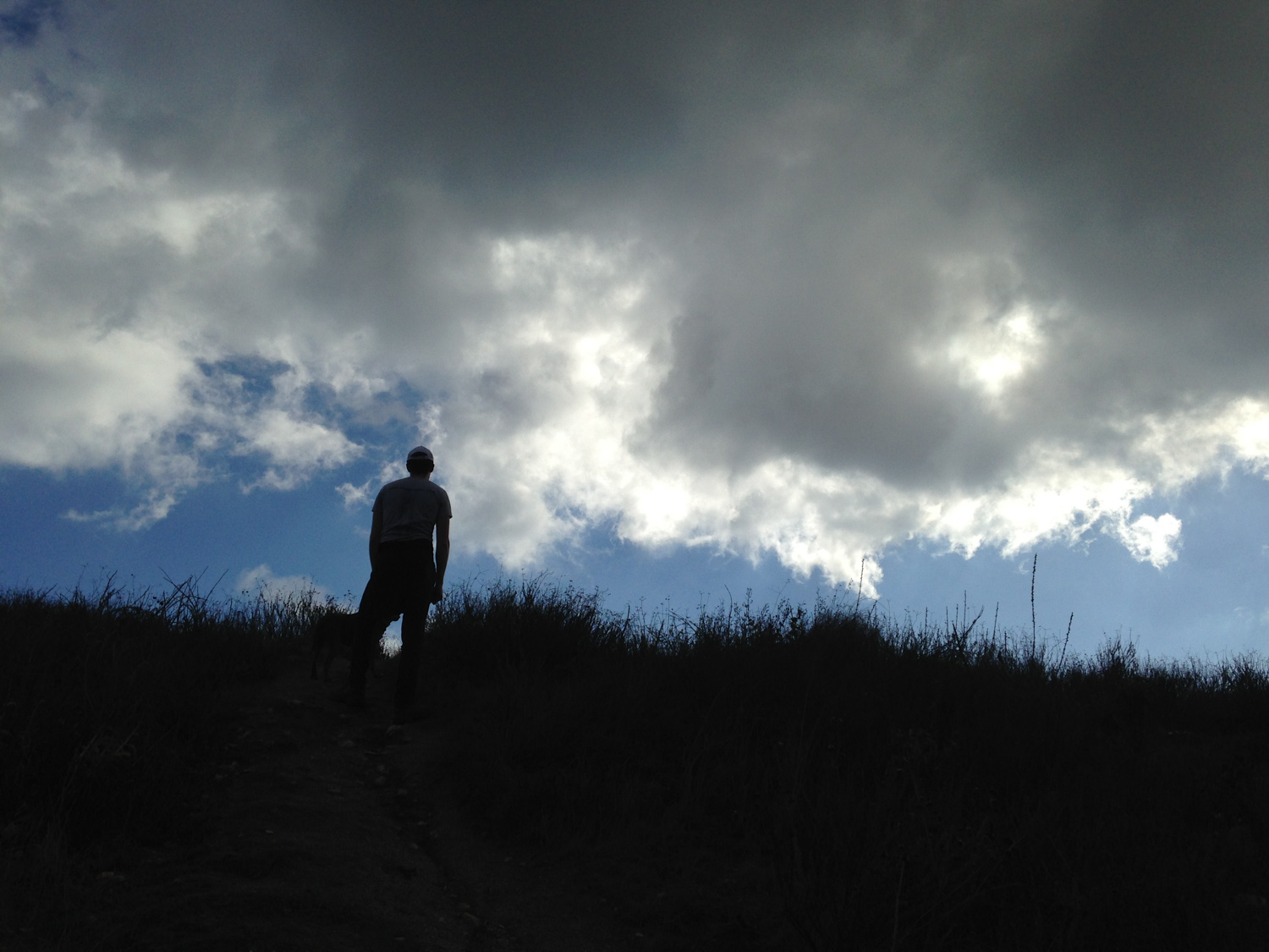 a hiker stands atop jones peak with the sky behind them